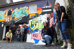 """Dr. Detmar Freyhoff (Schwerter Zahnärzte) vollendet selbst gekonnt das Graffiti der Projektgruppe """"VSI sagte danke"""" zu den Zahnärzten vor dem Streetlife. Links daneben: Peter Frenz (VSI-Projektkoordinator) und Frau A. Fitzner sowie (rechts stehend) Margarete Brand (VSI-Vorstand)."""